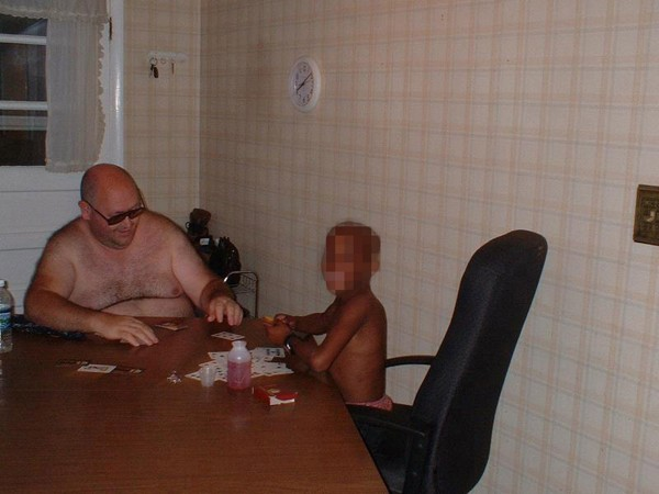Randy Winslow plays cards with the 10-year-old boy he and Nicole Eason obtained through the Internet from adoptive mother Glenna Mueller, who provided this undated family photo taken in 2006 in Appleton, Wisconsin. Winslow was later convicted of trading child pornography.