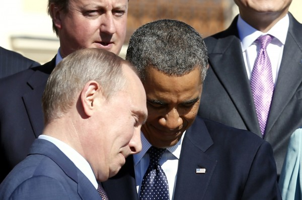 Russian President Vladimir Putin (L) walks past U.S. President Barack Obama during a group photo at the G20 Summit in St. Petersburg September 6, 2013. At top left is British Prime Minister David Cameron.