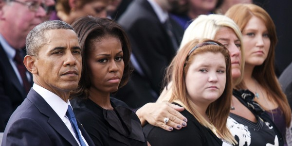 U.S. President Barack Obama (L) and First Lady Michelle Obama (2nd L) sit with families of victims of the Washington Navy Yard shooting at Marine Barracks during a memorial service in Washington September 22, 2013. Last Monday, a government contractor killed 12 people during rampage at the Washington Navy Yard before police killed him in a gun battle.
