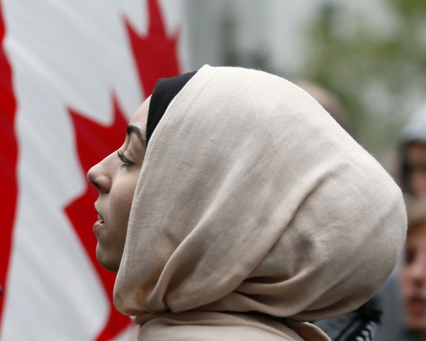 A demonstrator is framed by a Canadian flag as she protests against Quebec's proposed Charter of Values in Montreal, September 14, 2013. Thousands took to the streets to denounce the province's proposed bill to ban the wearing of any overt religious garb by government paid employees.