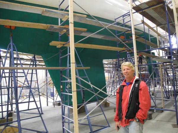 Front Street Shipyard President JB Turner in front of one of the yachts his company is refitting this season. A new, larger travel lift is allowing larger boats to use the growing facility.