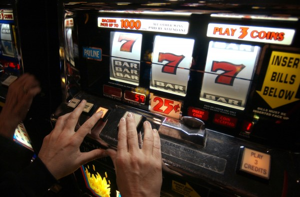 A woman keeps her hands on the buttons of a slot machine as the numbers and bars whirl by at Foxwoods Resort Casino in Ledyard, Conn.