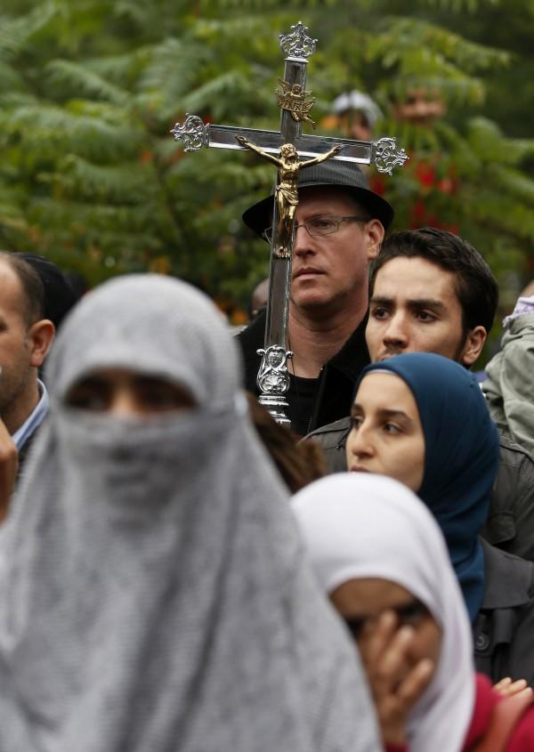 A man carries a cross during a protest against Quebec's proposed Charter of Values in Montreal, September 14, 2013. Thousands took to the streets to denounce the province's proposed bill to ban the wearing of any overt religious garb by government paid employees.
