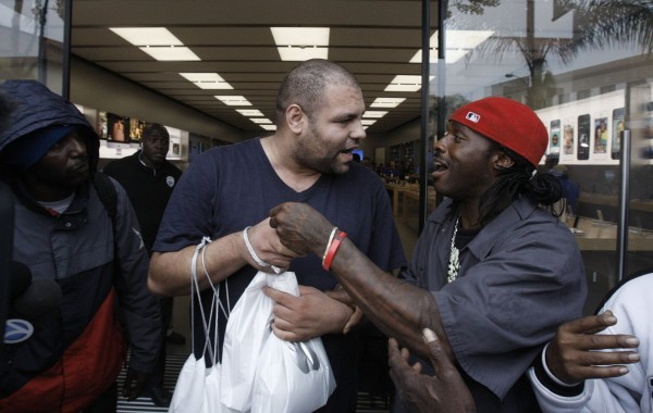 An unidentified man (right) who was a line-holder, confronts another man outside the Apple store on Friday, Sept. 20, in Pasadena, Calif. The man at right apparently had been hired by the other to purchase Apple's new iPhone 5s and when he was unable to do so, the man apparently refused to pay him.