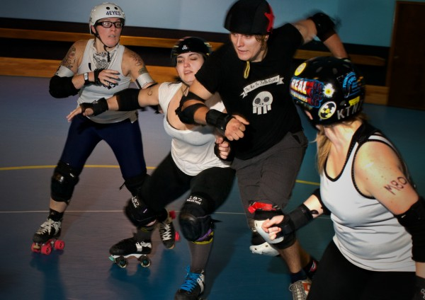 Women roller derby skaters help members of a new men's team get ready for their first bout in Portland Sunday night. From left is Amy Martin, &quotPunchy O'Guts,&quot Jodie Keenan, &quotBrannigan's Law,&quot Chris Ziobrowski, &quotFearUs Oxide,&quot and K.T. Long &quotKTNT.&quot The Casco Bay Gentlemen's Derby is set to play the Vermont Mean Mountain Boys October 5 at the Portland Expo.