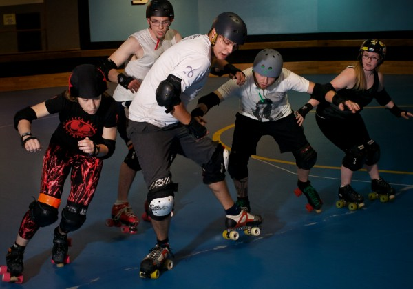 Women roller derby skaters help members of a new men's team get ready for their first bout in Portland Sunday night. From left is Sam Ellis, &quotZeldangerous,&quot Ryan Arnold, &quotMilhouse VanBouten,&quot Chris Ziobrowski, &quotFearUs Oxide,&quot Opie Helstrom and K.T. Long, &quotKTNT.&quot The Casco Bay Gentlemen's Derby is set to play the Vermont Mean Mountain Boys October 5 at the Portland Expo.