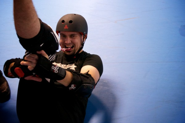 A.J. Caron stretches before practicing with the Casco Bay Gentlemen's Derby in Portland Sunday night. Caron founded the men's roller derby team three years ago with friend Anthony Oddi. The team will have its first Maine bout Saturday night at the Portland Expo.