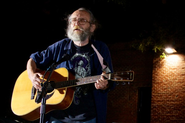 Jim Devine sings in Portland's Congress Square Park Friday night protesting the possible sale of the park to a private developer.