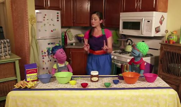 Monica Willey explains cooking to puppets Polo and Piper in the pilot episode of Monica's Mixing Bowl, a Web cooking show for kids.