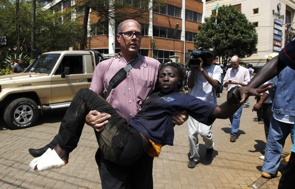 A journalist rescues a woman injured in a shootout between armed men and the police at the Westgate shopping mall in Nairobi on Saturday.