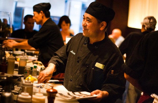 Chef Masa Miyake smiles during a dinner rush recently at his flagship restaurant, Miyake, on Fore Street, Portland. Miyake splits his time between his restaurants in Portland and his farm in Freeport, where he is raising heritage pig breeds to introduce to American palates.