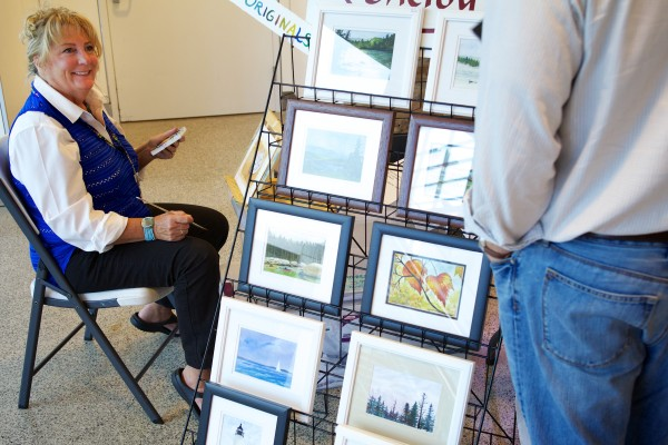 Jetport artist Shelby Crouse talks to a traveller while painting Monday at the Portland International Jetport.  Crouse and Carol Ann Szafranski, who are best friends and neighbors, have been selling their artwork in the jetport for three years.