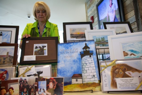 Jetport artist Carol Ann Szafranski straightens up her wares at a art kiosk in the Portland INternational Jetport Monday. Szafranski has been selling her art at the jetport for three years.