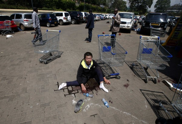 A wounded man sits screaming in shock at a parking lot of Westgate mall in Nairobi on Saturday, Sept. 21.