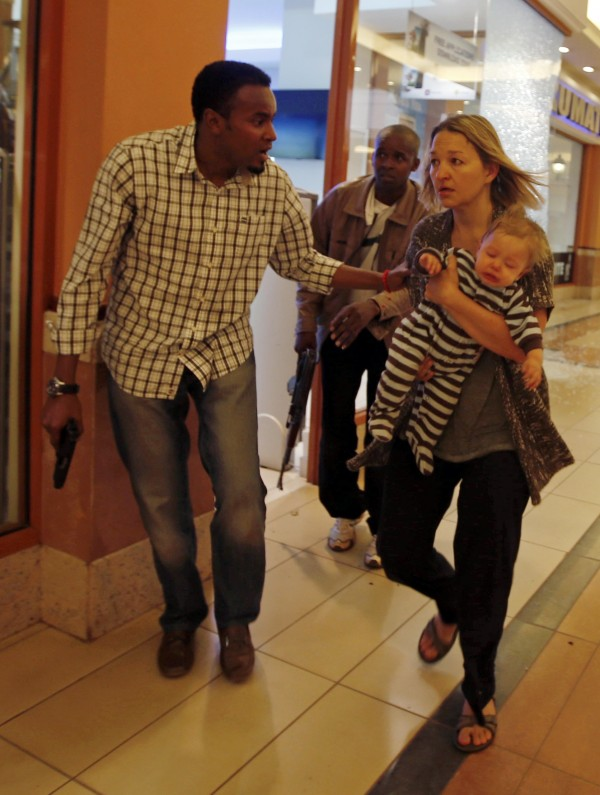 Armed police guide a woman carrying a child to safety at Westgate shopping center in Nairobi  on Saturday, Sept. 21.