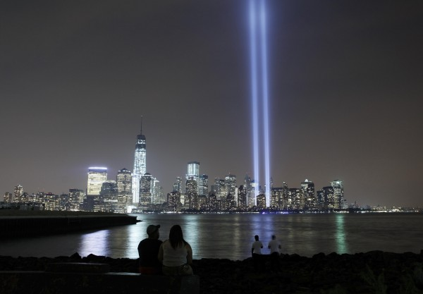 The Tribute in Light is illuminated next to One World Trade Center as people look across the Hudson River in Jersey City, New Jersey, September 11, 2013, marking the 12th anniversary of the September 11 attacks in 2001.