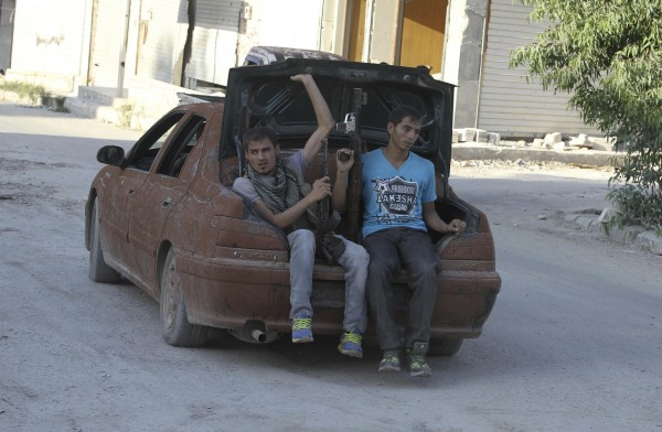 Free Syrian Army fighters sit on the back of a car driving toward the front line in Aleppo's Sheikh Saeed neighborhood, on Friday, Sept. 20.