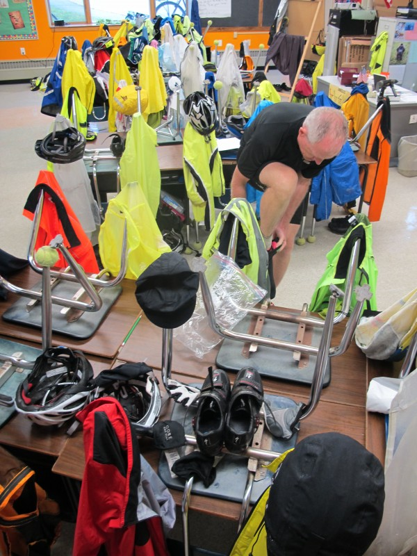 Wet bicycling clothes hang on upended chairs at Cave Hill School in Eastbrook on Friday, Sept. 13, 2013, as Brad Smith of Jaffrey, N.H., pulls on wet shoes after eating lunch the school. Smith was one of more than 250 experienced bicyclists who participated in the inaugural weeklong BikeMaine 2013 tour.
