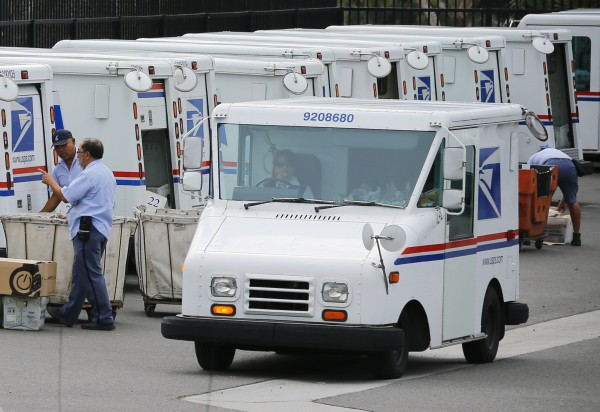 U.S. postal workers load their trucks with mail for delivery from their postal station in Carlsbad, Calif., on Feb. 6, 2013.