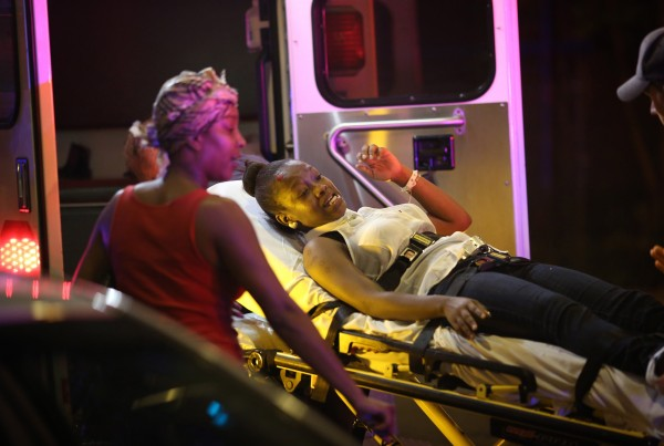 Emergency personnel transport victims from the scene where 12 people, including a 3-year-old, were shot at Cornell Square Park in the Back of the Yards neighborhood in Chicago, September 19, 2013.