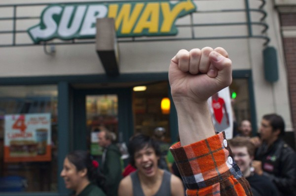 Stephen Baldwin holds his fist in the air outside a Subway restaurant during a strike aimed at the fast-food industry and the minimum wage in Seattle, Washington August 29, 2013. Fast-food workers went on strike and protested outside restaurants in 60 U.S. cities on Thursday, in the largest protest of an almost year-long campaign to raise service sector wages.