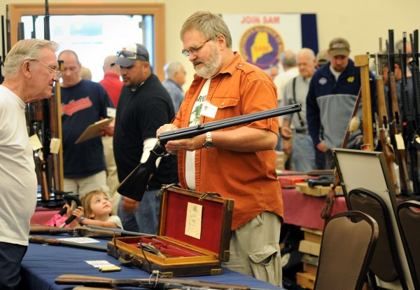 Bob Erickson shows a 1930's Olsen double rifle to a patron of the 2013 Annual Bangor Gun Show at the Cross Insurance Center Saturday morning.