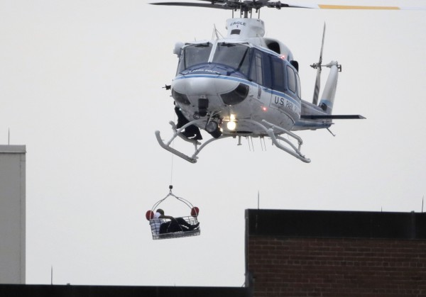 A helicopter pulls what appears to be a shooting victim up as it hovers over a rooftop on the Washington Navy Yard campus in Washington, September 16, 2013. The U.S. Navy said several people were injured and there were possible fatalities in the shooting at the Navy Yard in Washington D.C. on Monday. The Navy did not immediately provide additional details but a Washington police spokesman said earlier that five people had been shot, including a District of Columbia police officer and one other law enforcement officer.