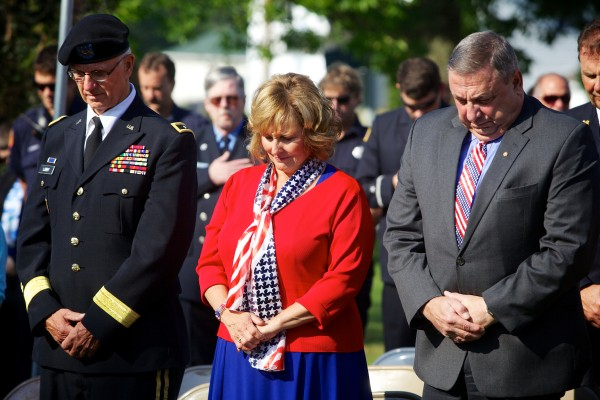 Paul LePage (from right), his wife, Ann, and Maj. Gen. John W. Libby, former adjutant general of the Maine National Guard, bow their heads in prayer at a ceremony Wednesday morning marking the anniversary of Sept. 11, 2001, in Freeport.