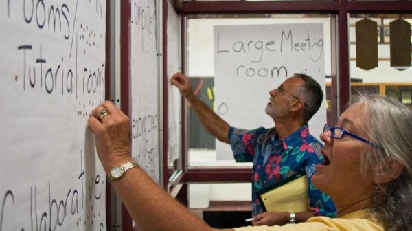 Bob Stier, president of the Thomas Memorial Library Foundation, and Rachel Perry, an avid library user, prepare posters during a public forum about the future of the Cape Elizabeth library on Aug. 29.