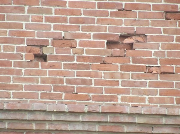 Detail of brick facade showing damage near the top of the building.