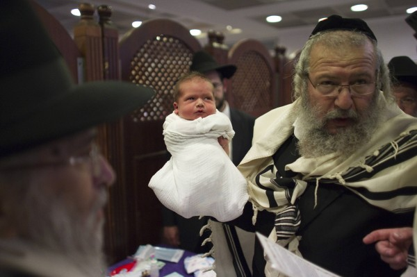 Rabbi Chaim Moshe Weisberg, a mohel or a Jewish ritual circumciser, holds a baby after circumcising him in Jerusalem in this September 24, 2012 file photo. Circumcision is one of Judaism's most important laws and for generations of faithful it has symbolised a Biblical covenant with God. But in Israel, more and more Jewish parents are saying no to the blade.