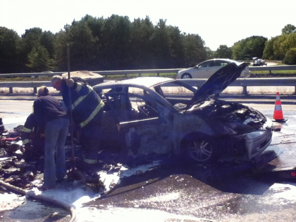 A burned-out car sits on the side of the eastbound lanes of Interstate 395 in Bangor on Tuesday morning.