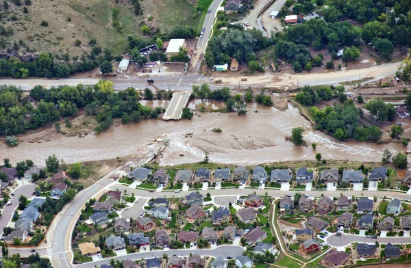 An aerial view shows flood waters and a washed-out road adjacent a suburban neighborhood in Lyons, Colorado September 13, 2013. National Guard troops plucked stranded residents out of danger by helicopter and hauled them out of an inundated community in military trucks Friday.