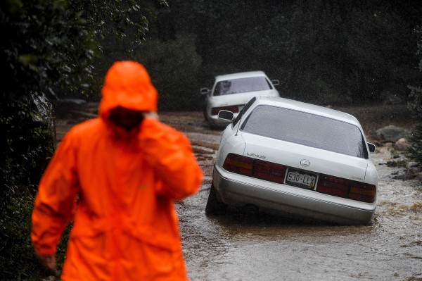Cars sit in a flooded driveway as Cheyenne Creek flows over its banks and into the surrounding creek side properties in Colorado Springs, Colorado, Friday, September 13, 2013.