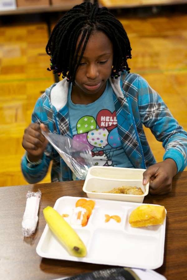 Larissa Thomas, 10, unwraps hot chicken for lunch at Longfellow Elementary School in Portland Thursday. School meals are made from scratch in a new, central facility, portioned onto trays, topped with plastic, trucked to each school and reheated on site. During the prior three decades, school meals sat in a warmer all day.