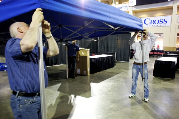 Lou Fraser (from left) and Darby Higgins of Friend and Friend ATV  set up a tent inside the Cross Insurance Center Friday morning in preparation for the BDN Maine Man Expo.