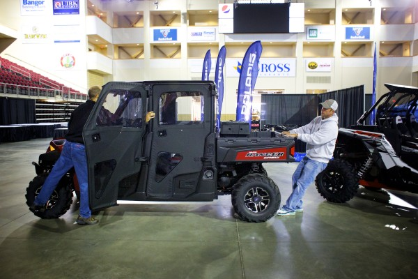 Jeff Horne (from left) and Darby Higgins of Friend and Friend ATV move a Polaris Ranger side by side into place in preparation for the BDN Maine Man Expo Friday morning in Bangor.
