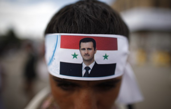 A protester loyal to the Shi'ite Muslim Al-Houthi group, also known as Ansarullah, wears a headband with a picture of Syria's President Bashar al-Assad as he attends a demonstration against potential strikes on the Syrian government, in Sanaa September 6, 2013.