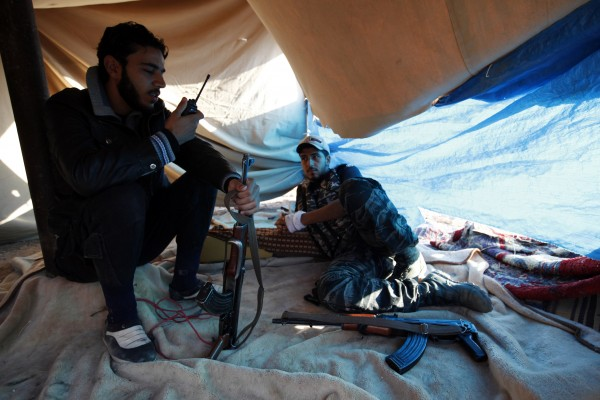 Free Syrian Army fighters rest as one of them uses a talkie-walkie near the the Kwers military airport, where forces loyal to Syria's President Bashar al-Assad are based, in Aleppo September 9, 2013.