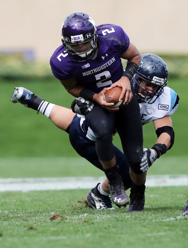 Northwestern Wildcats quarterback Kain Colter (2) is tackled by University of Maine Black Bears linebacker Zachary Hume (44) during the first quarter at Ryan Field in Evanston, Ill.