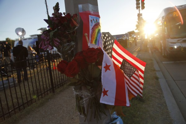 Flowers, flags and a child's drawing are pictured at a makeshift memorial outside the Navy Yard two days after a gunman killed 12 people before police shot him dead, in Washington, September 18, 2013. U.S. lawmakers are calling for a review into how Aaron Alexis, the suspected shooter in Monday's rampage at the Washington Navy Yard, received and maintained a security clearance, despite a history of violent episodes.