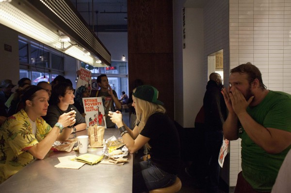 Patrons sit as their lunch is interrupted by demonstrators including Ethan Dittrich-Reed, right, in Chipotle Mexican Grill during a strike aimed at the fast-food industry and the minimum wage in Seattle, Washington August 29, 2013.