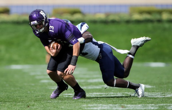 Northwestern Wildcats quarterback Trevor Siemian (13) is tackled by University of Maine Black Bears defensive back Axel Ofori (1) during the first quarter at Ryan Field in Evanston, Ill.