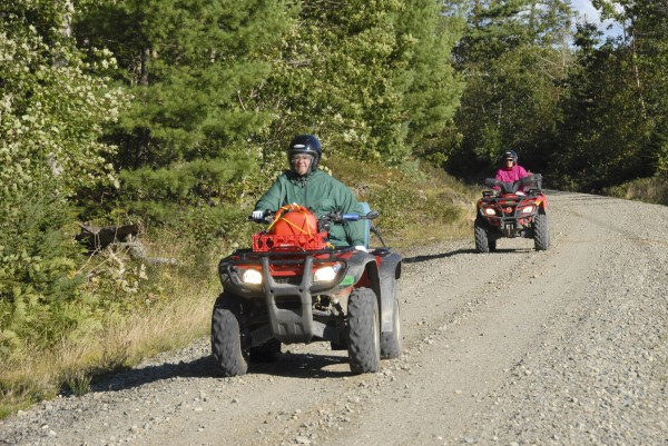 Two women on ATVs round a curve Sept. 8, 2013, near Mile Marker 15 along the Down East Sunrise Trail in Sullivan.