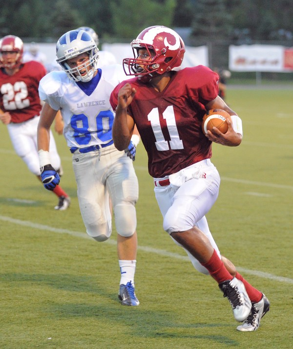 Bangor High School quarterback Xavier Lewis (right) scrambles for yardage as he is pressured by Lawrence High School's Chad Martin during the first quarter of an exhibition game in Bangor last Friday.