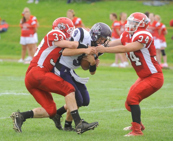 John Bapst High School's Spencer Baron (center) is tackled by Dexter Regional High School's Ethyn Gould (left) and Adam White during the game in Dexter on Saturday.