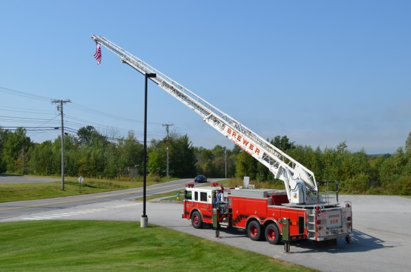 A Brewer Fire Department ladder truck displays the American flag along Parkway South in remembrance of the Sept. 11 terrorist attacks in 2001. Several people driving by honked their horns on Wednesday.