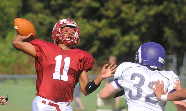 Bangor's quarterback Xavier Lewis (left) prepares to throw a pass as he is pressured by Deering's Dan Marzilli during the first half of the game in Bangor on Saturday.