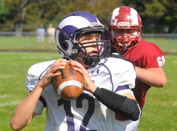 Deering's quarterback Max Chabot (left) looks to throw a pass as he is pressured by Bangor's Erick Hoover during the first half of the game in Bangor on Saturday.