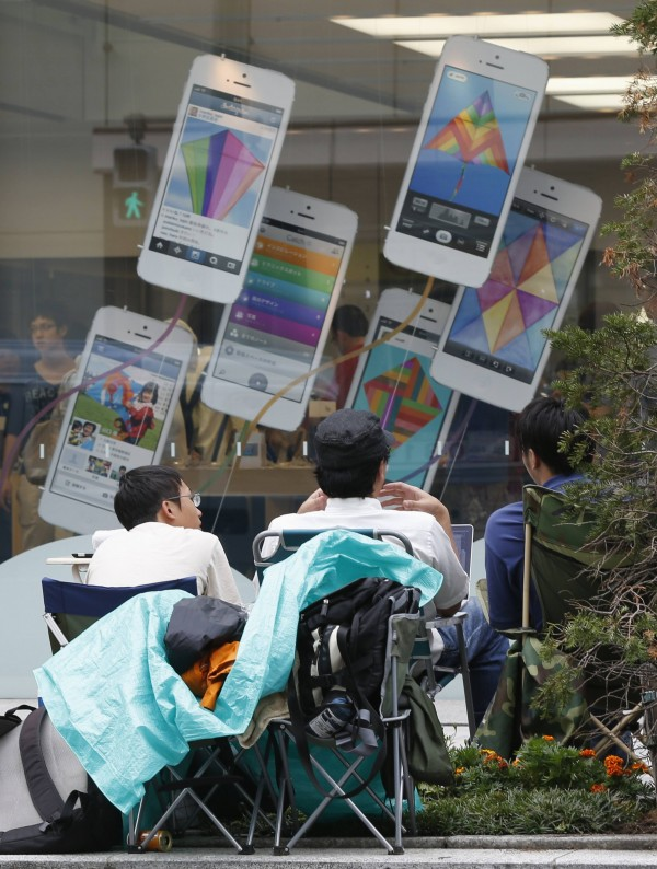 Men sit on foldable chairs as they begin camping ahead of the Sept. 20 release of iPhone 5S, in front of an Apple Store at Tokyo's Ginza shopping district Sept. 11, 2013. Apple Inc unveiled on Tuesday an iPhone with a fingerprint scanner to help it stand out in a crowded field of similar smartphones, plus a cheaper plastic model for emerging markets that proved pricier than expected.
